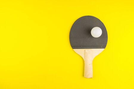Table tennis racket with ball on yellow background.Concept sport.