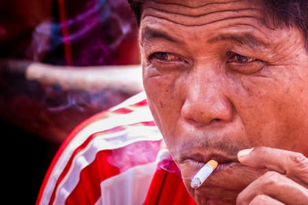 Bangkok, Thailand - October, 06, 2019  : Unidentified man relaxing, sitting and smoking a cigarette at Bangkok, Thailand
