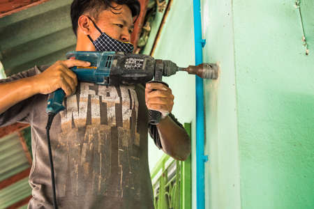 Bangkok, Thailand - June, 22, 2020 : Unidentified name strong man in working close-up. Builder with a drill demolishes a brick wall for installing the air conditioner of the house at Bangkok, Thailand