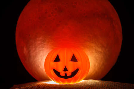 The Horror or scary pumpkin for Halloween Day.There's a red full moon in the background. Halloween horror concept.