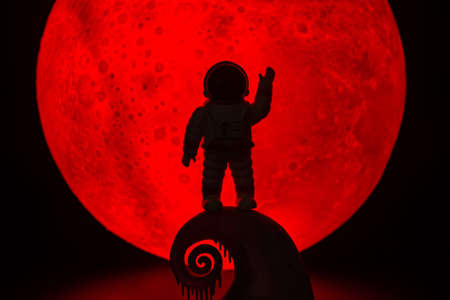 The silhouette of The Astronaut man .There's a red full moon in the background. Halloween horror concept. 写真素材