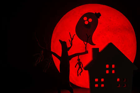 The silhouette of a tree standing dead with a man hanged dead to the bone, Ghost spirit and Horror haunted house.There's a red full moon in the background. Halloween horror concept. 写真素材