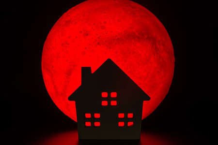 The silhouette of a Horror haunted house. There's a red full moon in the background. Halloween horror concept.