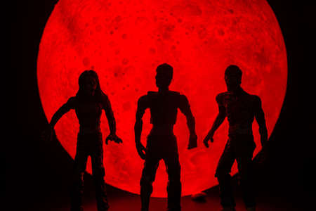 The silhouette of Halloween zombies decorations.There's a red full moon in the background. Halloween horror concept. 写真素材