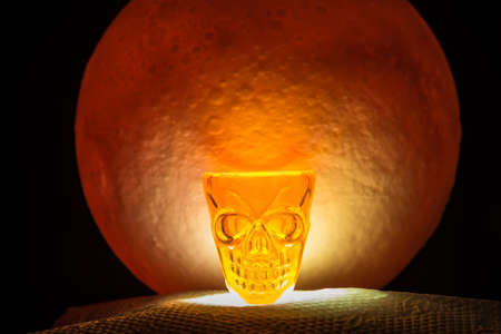 The Skull glass for Halloween Day.There's a red full moon in the background. Halloween horror concept.