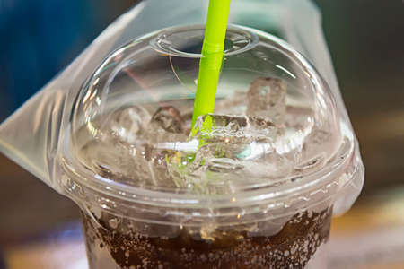 aerated soft drink with ice in plastic glass