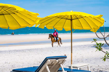 Prachuap Khiri Khan, Thailand- April, 03, 2021 : People horseback riding at Hua hin beach on hot sun during the day in Hua Hin, Thailand.Looking for customers to rent horses to ride on the beach.