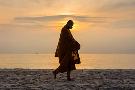 Prachuap Khiri Khan, Thailand- April, 04, 2021 : Sunrise with reflection on the sea and beach that have blurred silhouette photo of buddhist monk walking alms offering food in the morning on beach of Thailand. Editorial
