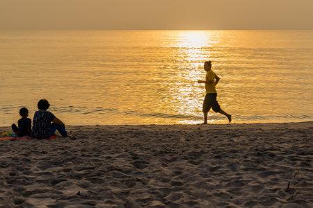 Prachuap Khiri Khan, Thailand- April, 04, 2021 :Silhouette of man athlete on sunset/sunrise seaside background, concept of endurance, strength, healthy lifestyle