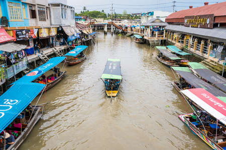 Samut Songkhram, Thailand - April, 04, 2021: Tourists shopping and boat ride around in Amphawa floating market. It is one of the most popular floating markets in Thailand.Many tourists come to travel much less due to the coronavirus outbreak.