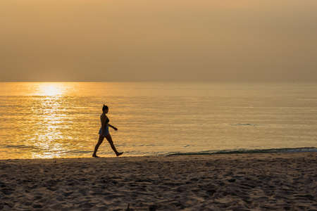 Prachuap Khiri Khan, Thailand- April, 04, 2021 :Silhouette of female athlete on sunset/sunrise seaside background, concept of endurance, strength, healthy lifestyle