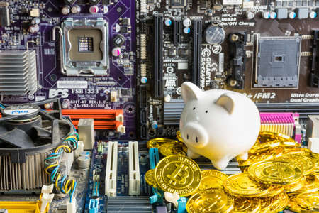 Bangkok, Thailand - March, 22, 2021 :Piggy bank and stack of Bitcoin coins on Computer motherboard .Concept of business and finance concept. save money concept.Bitcoin finance in the digital age Editorial