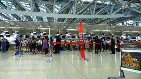 check in: Passengers waiting to check in at the airport .