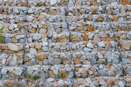 tied together: The gabion walls  are retaining wall made of stacked stone-filled gabions tied together with wire,Thailand Stock Photo