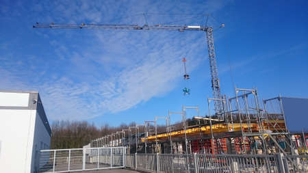 Large construction site with crane on which a cement mixer hangs in bright blue sky