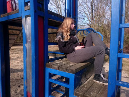 Teenage boy sits with a beer bottle on the climbing frame of a playground Standard-Bild