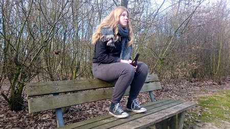 Teenager sits with a beer bottle on the back of a park bench with blank look into the distance Standard-Bild