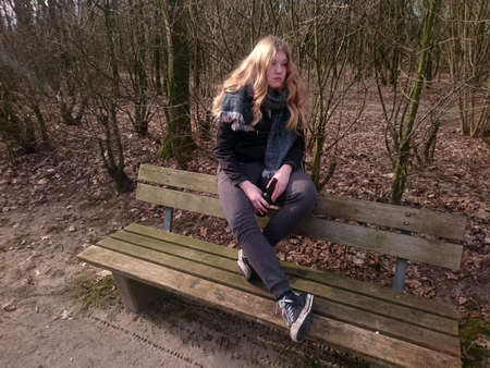Teenage girl with desolate look is sitting with a beer bottle of a park bench
