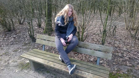 Teenage girl is sitting with a beer bottle on a park bench Standard-Bild