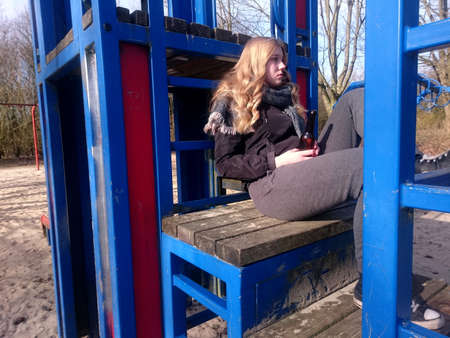 Teenage girl with sad look is sitting with a beer bottle on a climbing frame of a playground