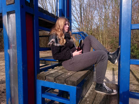 Adolescent with a defiant look sits with a beer bottle a climbing frame of a playground