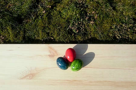 Easter eggs on a light wooden board lying on moss