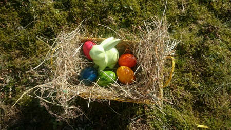 Easter basket with colorful eggs and Easter bunnies made of porcelain