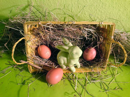 Easter basket filled with hay, brown eggs and a decorative rabbit with green background