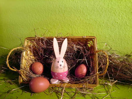 Basket with straw, brown eggs and a decorative rabbit with green background
