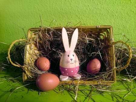 Basket with hay, brown eggs and a decorative bunny with green background