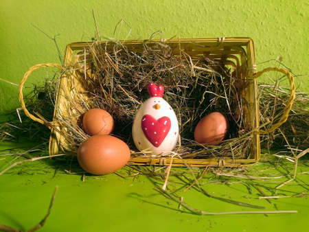 Easter basket filled with hay and brown eggs and a decorative chicken with a green background Standard-Bild