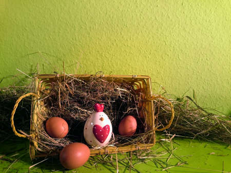 Easter basket filled with hay and brown eggs and a decorative chicken with green background