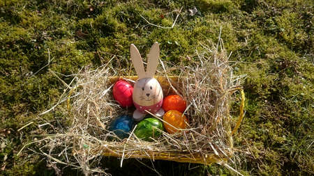 Easter basket with colored eggs and decorative bunnies on a meadow overgrown with moss