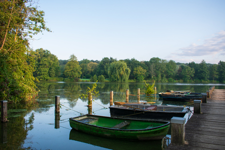 Lake with jetty and old rowboats. Location: Germany, North Rhine Westphalia, Hoxfeld
