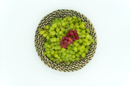 Green and red grapes in a basket.