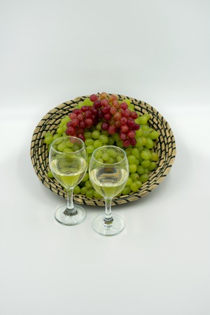 fresh greens and red grapes in a basket with white wine glasses.