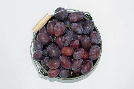 delicious plums in a decorative small bucket. View from above.Studio shot on white background Standard-Bild - 108816944