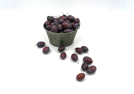 delicious plums in front of and in a decorative small bucket.