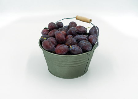 delicious plums in a decorative small bucket.
