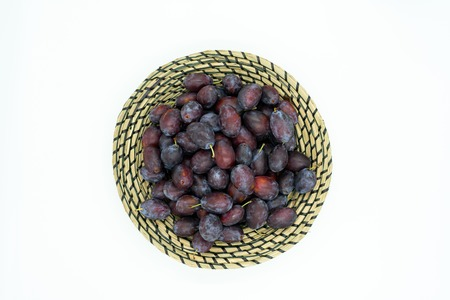 delicious plums in a decorative bast basket, top view.