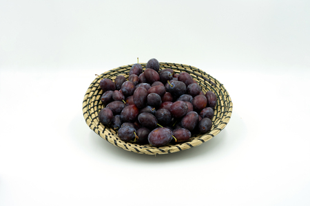 delicious plums in a decorative bast basket.