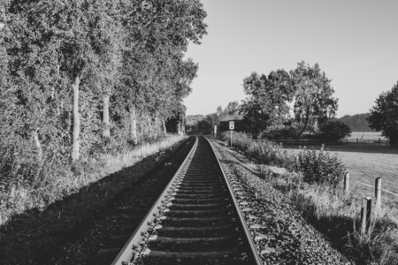 Black and white image of railway track in rural area Location: Germany, North Rhine-Westphalia Standard-Bild - 109581695