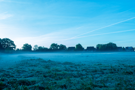 Misty swath in the early morning with village in the background.Location: Germany, North Rhine - Westphalia, Borken Standard-Bild - 109581705