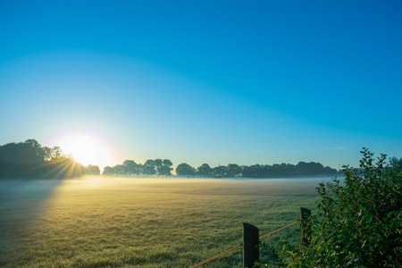 beautiful sunrise with morning mist on the fields. Location: Germany, North Rhine - Westphalia, Borken - Marbeck Standard-Bild - 109581712