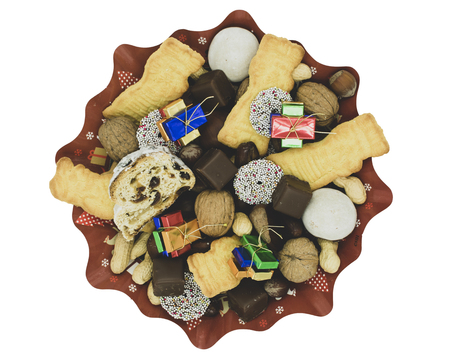 Christmas plate with different varieties of cookies, chocolate and nutsTop view, isolated on white Standard-Bild - 110709188