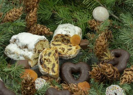 Christmas stollen and various Christmas treats on fir branches.Studio shot of baked apple and butterstollen Standard-Bild - 110710848