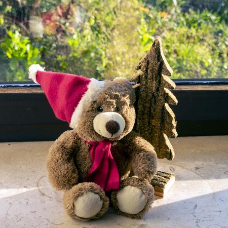 Christmas teddy bear with christmas tree on the windowsill Standard-Bild - 117804030