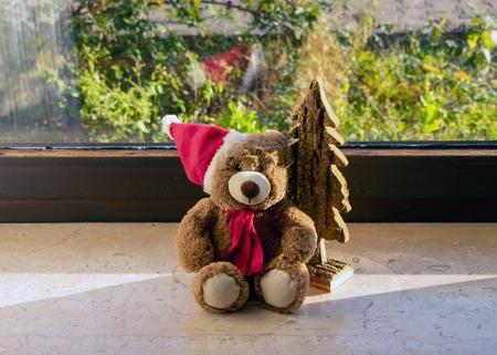 cute teddy with santa hat on the windowsill Standard-Bild - 117804033