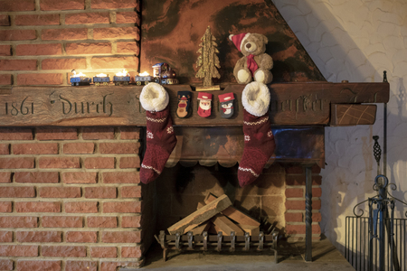 Rustic fireplace with Christmas train with burning candles and Christmas stockings Standard-Bild - 117804038
