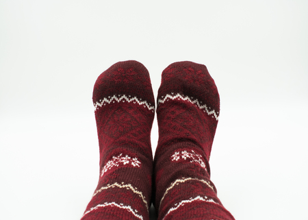 Feet with christmas socks on white background Standard-Bild - 117804050